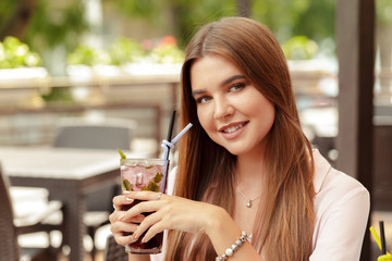 Portrait of delightful young woman holding glass of cold refreshing cocktail
