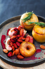 Baked sweet yellow apple with nuts and  berry in sugar glaze