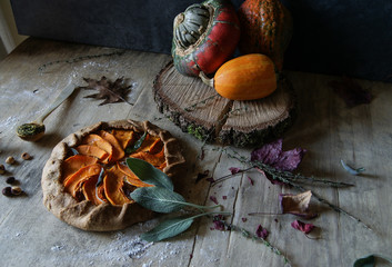 Baked pumpkin galette with sweet onions on wooden table