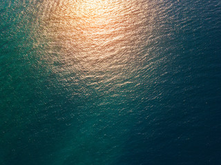 Wall Mural - Sea surface aerial view with yellow sun reflection