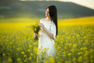 Happy young woman with bouquet of wildflowers in yellow field in sunset lights, summer time