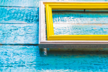 yellow frame inside a white frame for photos and images with a blank space inside on a blue textured wooden wall