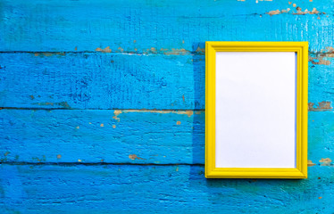 frame for photographs and images of yellow color with a blank white background inside on a blue textured wooden wall