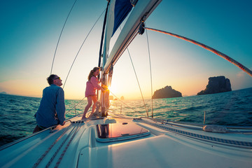 Couple of young sailors, man and woman, works with rope on the bow of the sailing boat at sunset