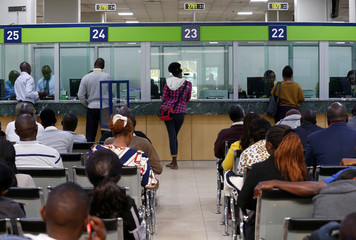 Customers are served as others wait in the banking hall at the Kenya Commercial Bank, Kencom branch in Nairobi