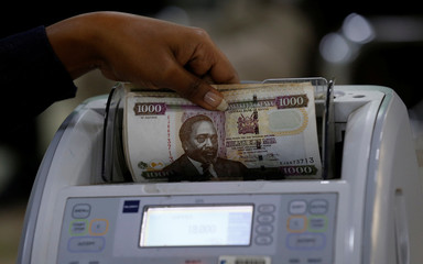 A Kenya Commercial Bank Mtaani agent counts Kenya shilling notes on a money counting machine as she serves a client inside in the banking hall at the Kencom branch in Nairobi