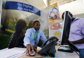 A Kenya Commercial Bank worker serves a customer in the banking hall at the Kencom branch in Nairobi