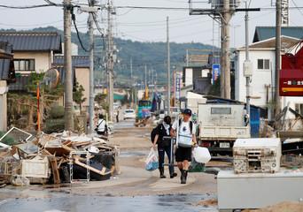 Local residents walk in a flooded area in Mabi town in Kurashiki