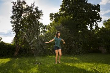 Girl having fun with lawn sprinkler in the garden