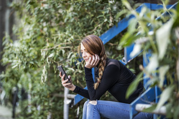 Smiling woman sitting on stairs looking at smartphone