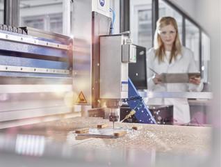 Female technician controlling CNC milling machine
