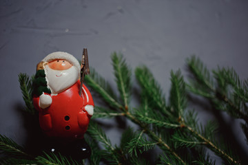 fir branch and toy Santa Claus on dark background, copy space
