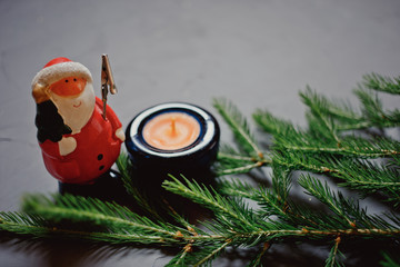 fir branch, candle and Santa Claus on dark background
