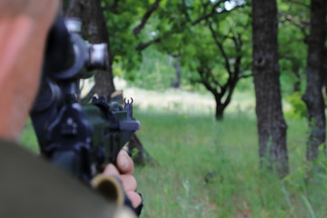 The hunter is aiming at the gun. Sighting the gun barrel at the target.