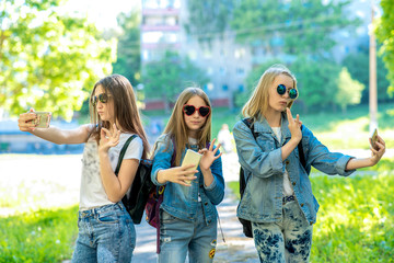 Three teenage girls. In denim clothes. Summer in nature. In his hands holds a smartphone. Communicates on the Internet through a videoconference. Video call on the phone. Photograph on a smartphone.