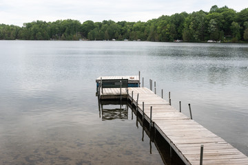 Wooden dock and a bench on a quiet lake