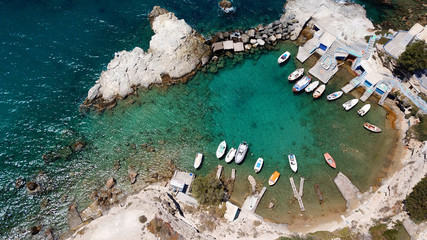 Aerial drone bird's eye view photo of picturesque small fishing harbor of Mandrakia with boat houses called syrmata and fishing boats docked on turquoise clear waters, Milos island, Cyclades, Greece