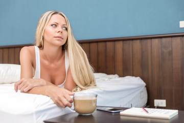 Young blonde woman drinks morning coffee in bed