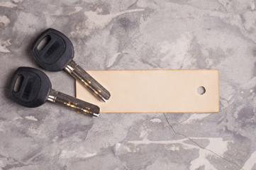 Two shiny metal keys with black plastic handle and blank rectangle paper on old gray dirty cement floor. Estate concept