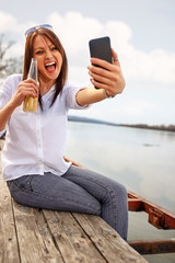 Girl taking selfie by the river while holding beer on a relaxing day out in nature
