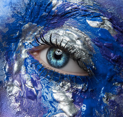 Macro and close-up creative make-up theme: beautiful female eye with blue, purple and silver paint wet