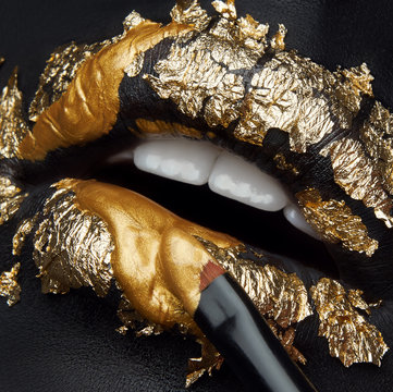 Macro and close-up creative make-up theme: beautiful female lips with black leather and gold foil and gold paint and brush