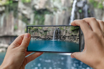 Taking Photo of Cheonjeyeon Waterfall on Jeju Island, (South Korea) with Mobile Phone. Active Tourism in Asia