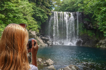 Young Female Tourist Taking Photo of Cheonjeyeon Waterfall on Jeju Island, South Korea
