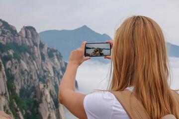 Caucasian Female Tourist Taking Photo of Ulsanbawi Rock. Mountain in Seoraksan National Park, South Korea