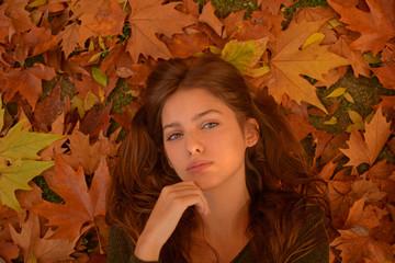 bella mujer tumbada sobre un manto de hojas