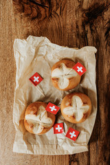Swiss bread buns called in German 1. Augustweggen baked in Switzerland to celebrate Swiss National Day on August 1st. Swiss flag with white cross on red background.
