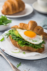 croissant sandwich with avocado and arugula for breakfast