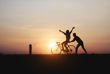 Silhouette of couple are cycling happily in time for sunset.