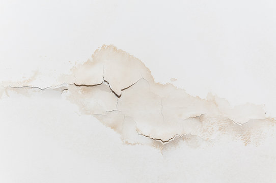 Big wet spots and cracks on the ceiling of the domestic house room after heavy rain and lot of water