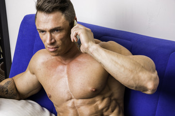 Handsome shirtless muscular bodybuilder man making a call with cell phone while laying on couch