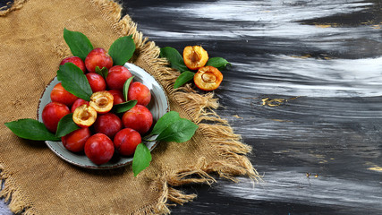 plums. red sweet plums with green leaves on a round plate and old cloth on a dark background. Flat lay, space for text