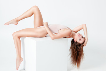 Fitness woman with a beautiful body posing over white background. Fitness, diet and beauty concept.  Pretty young woman sitting on cube.