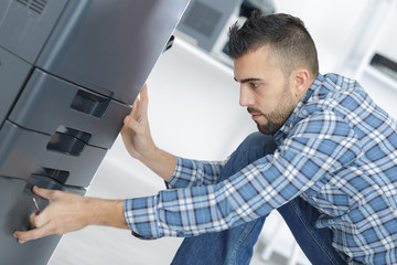 man fixing cartridge in printer machine at office
