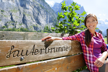 Wall Mural - Switzerland Alps summer travel Asian tourist woman smiling relaxing sitting on wooden bench with the word