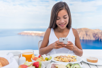 Food selfie social media vlogging girl taking photo with phone of breakfast plate using cellphone app. Luxury travel vacation lifestyle. Beautiful model in resort in Santorini, Greece, Europe.