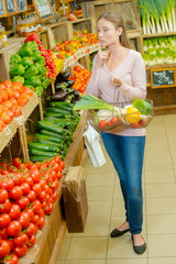 Woman proudly holding up a basket of vegetables