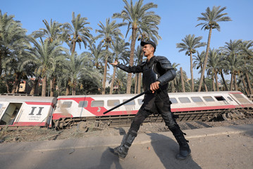 A police officer stands guard in front of a passenger train which derailed in al-Badrasheen area of Giza province, south of Egypt's capital Cairo