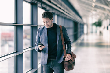 Mobile phone business man walking in airport with messenger bag using cellphone texting sms message on smartphone app - businesspeople commute lifestyle. Young professional businessman.