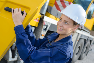 Lady at cab of heavy plant vehicle