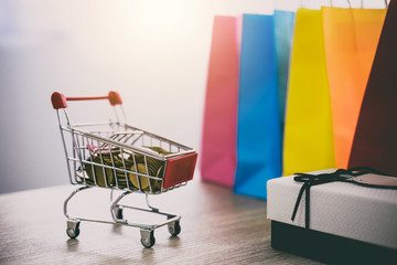 Model of Shopping Cart on wooden floor and gift box and shopping bag, Online payment and shopping concept