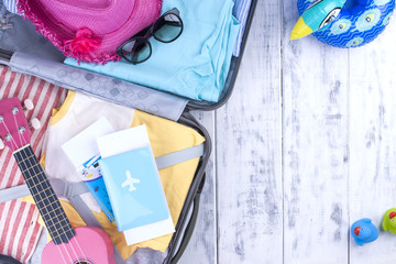 Suitcase for vacation, clothing and passport. Accessories for the sea and rest. Bright colors. Copy space.