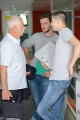 professor talking to two students in corridor