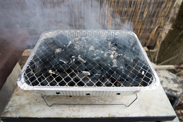 Small Grill coal in fire with smoke