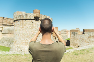 man taking a picture of the Fort de Salses, France