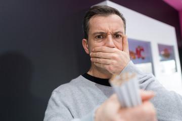 portrait of man sick looking at cigarettes